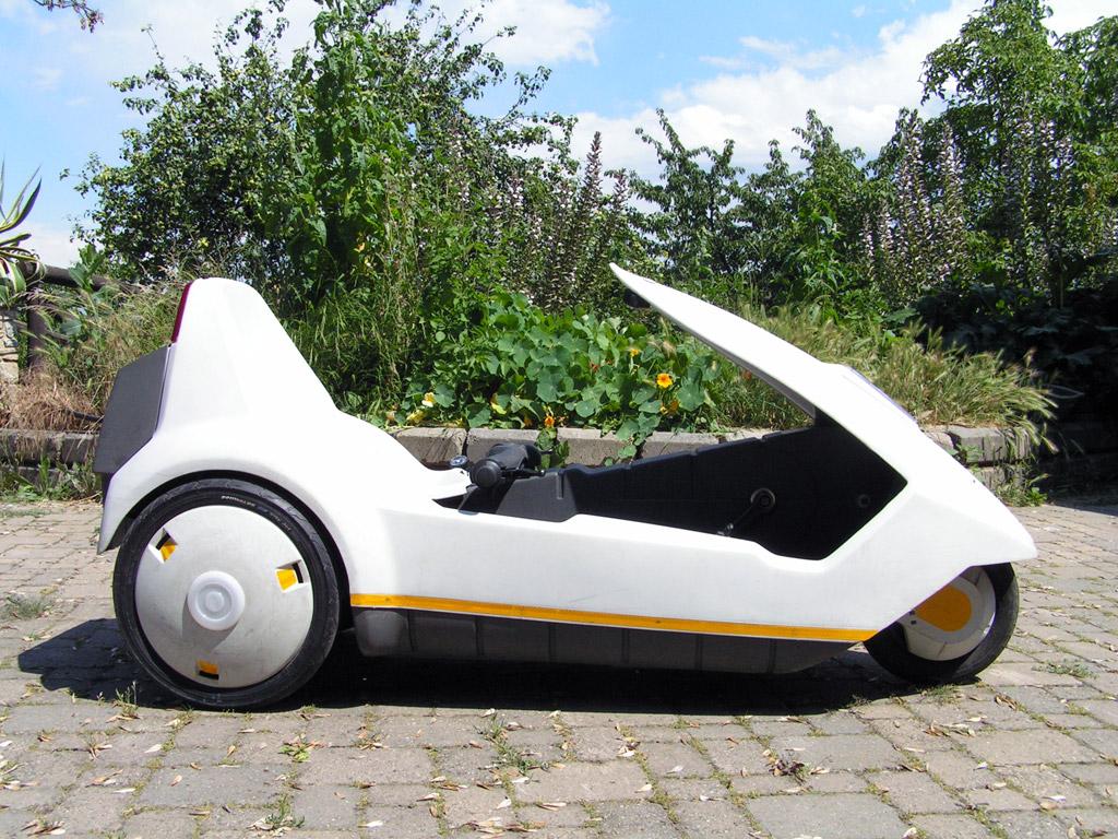SINCLAIR C5 - pojazd elektryczny, stworzony w 1985 roku. Kosztował wówczas 399 funtów.  By Myself - Photo of my C5 in the backyard - after restoration project, GFDL, https://commons.wikimedia.org/w/index.php?curid=9641052