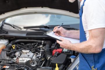 Car mechanic checking a car engine