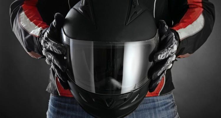 Motorcyclist with helmet in his hands. Dark background
