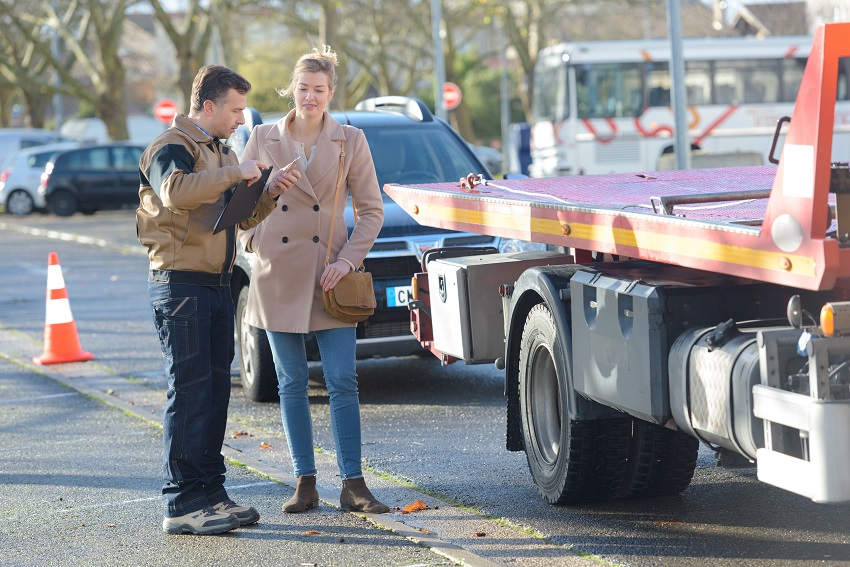 a young women and tow truck driver talking